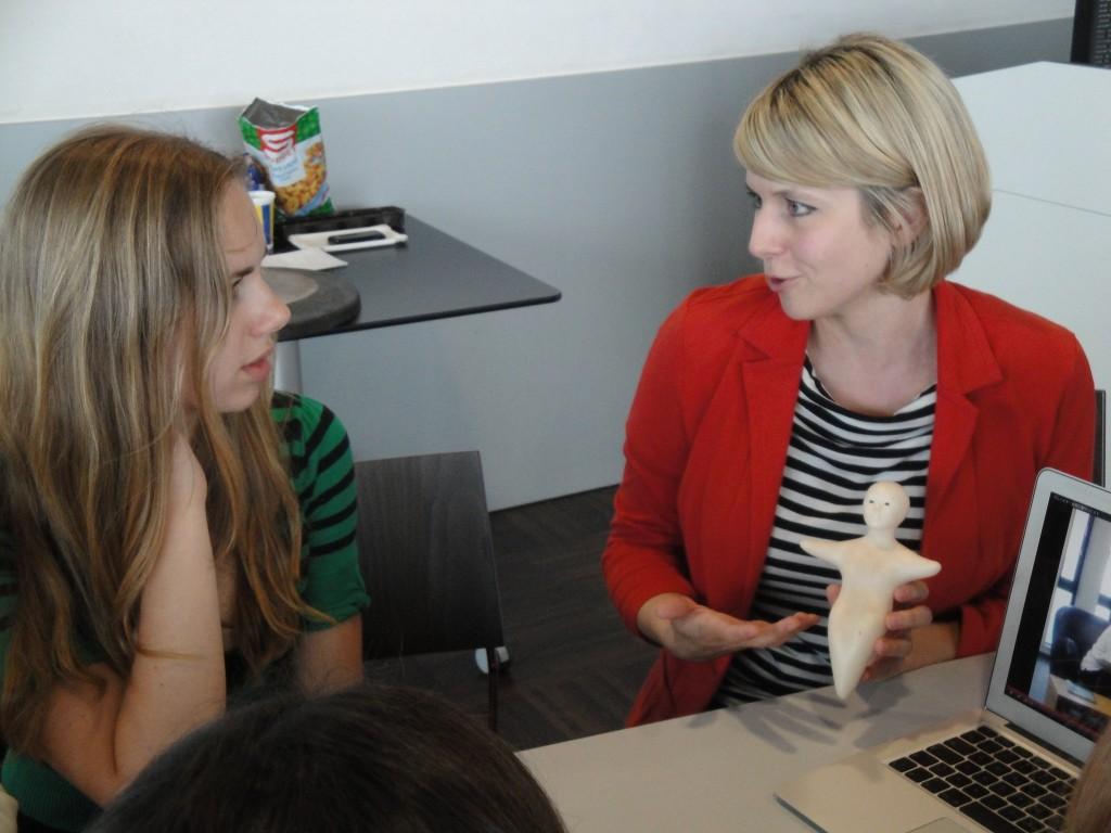 Roboterforscherin Martina Mara mit einem robotermodell in Gespräch mit Jugendlichen