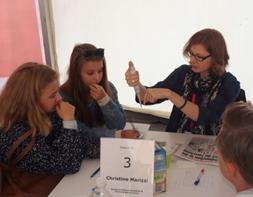 Christine Marizzi zeigt ihren Forschungsgegenstand, eine Pipette, den Jugendlichen