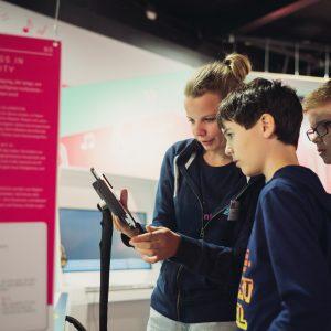 junge Dame liest gemeinsam mit zwei Burschen den Ausstellungstext eines Exponates