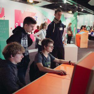 Jugendliche probieren eine Station auf der MS Wissenschaft aus