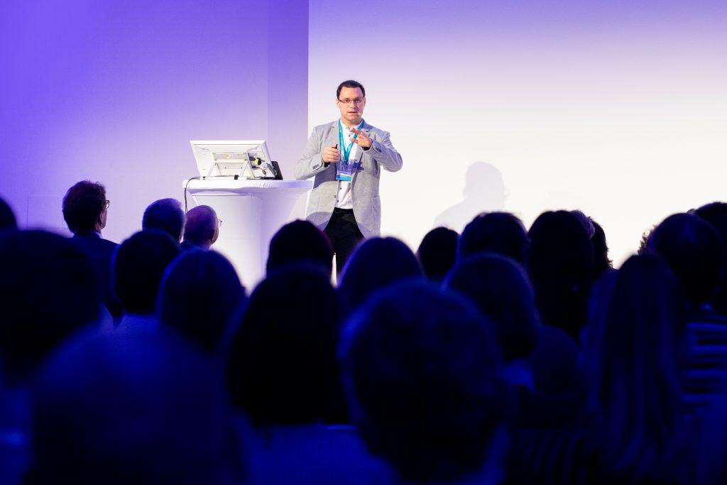 Präsentation von Armin Kirchknopf bei seinem Pitch. Im Vordergrund sind die ZuhörerInnen mit demRücken zur Bühne zu sehen. Im Hintergrund ist Armin Kirchknopf zu sehen.