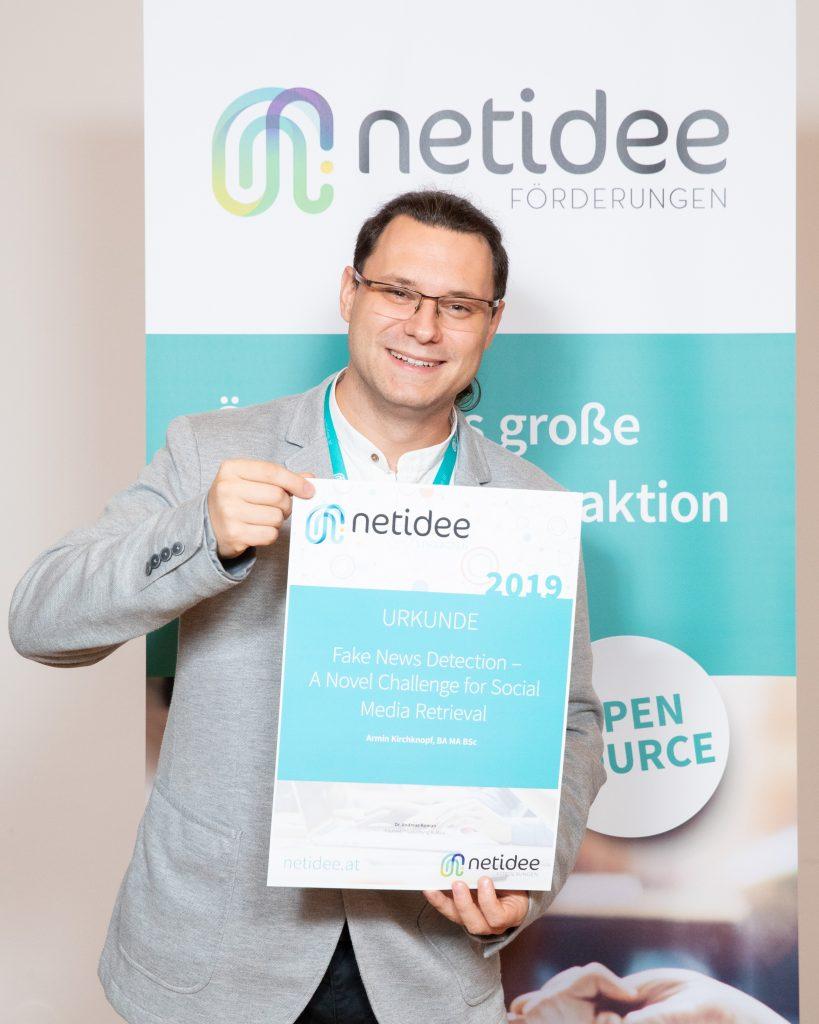 Armin Kirchknopf präsentiert die Urkunde vom Wettbewerb Netidee 2019 - im Hintergrund ist das Rollup der Initiative netidee zu sehen.
